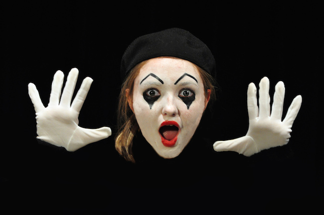 Image of a mime staring at camera, mouth agape and hands open with palms facing camera
